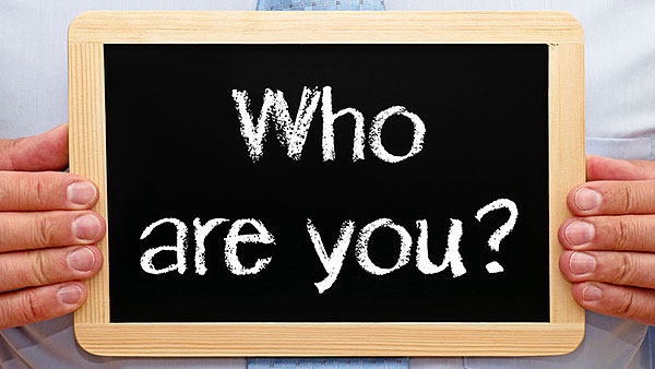 "person holding chalkboard with the words ""who are you"" on it"