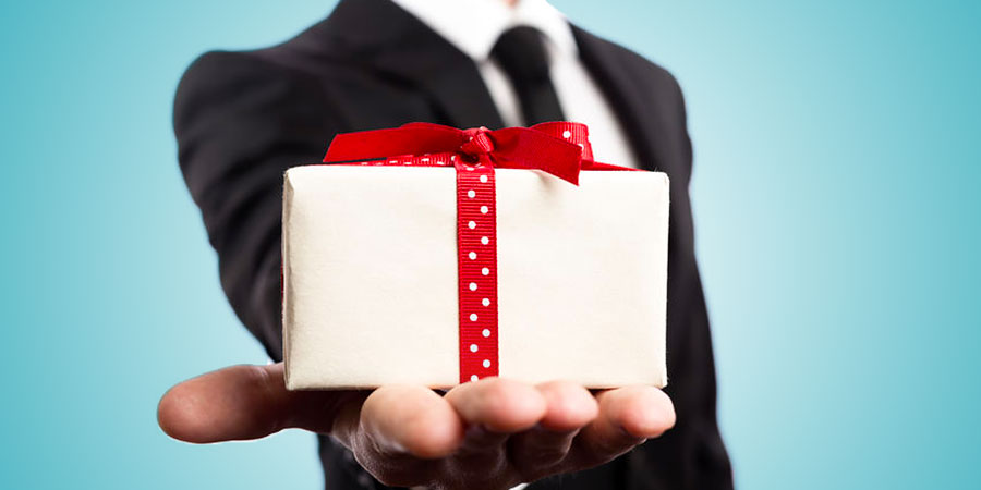 Business man holding a gift with a ribbon on it.