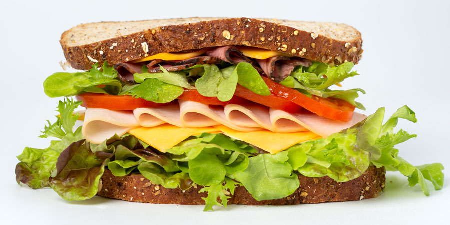 A large sandwich with lunch meat, cheese, lettuce and tomato.