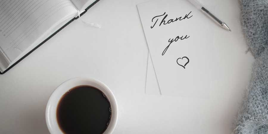 A handwritten thank you note next to a cup of coffee.