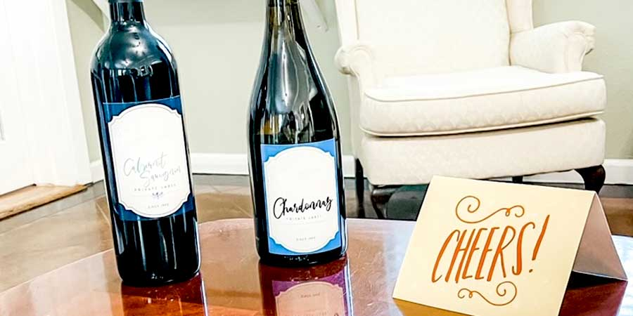 """Two wine bottles sitting on a desk with a card that says """"Cheers"""""""